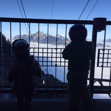 Our two daughters marveling at the sunlit cable car arising from the sea of fog