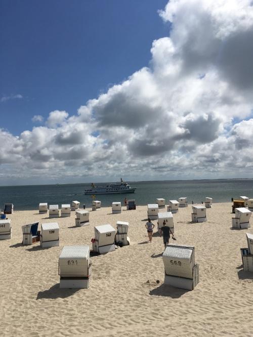 Roofed wicker beach chairs on a sandy beach in Hörnum on the island Sylt